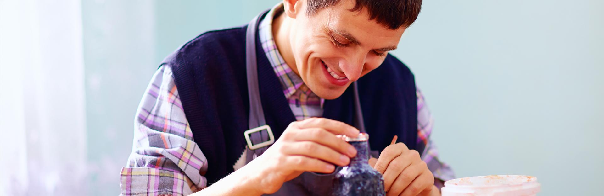 Un hombre con discapacidad realiza manualidades.