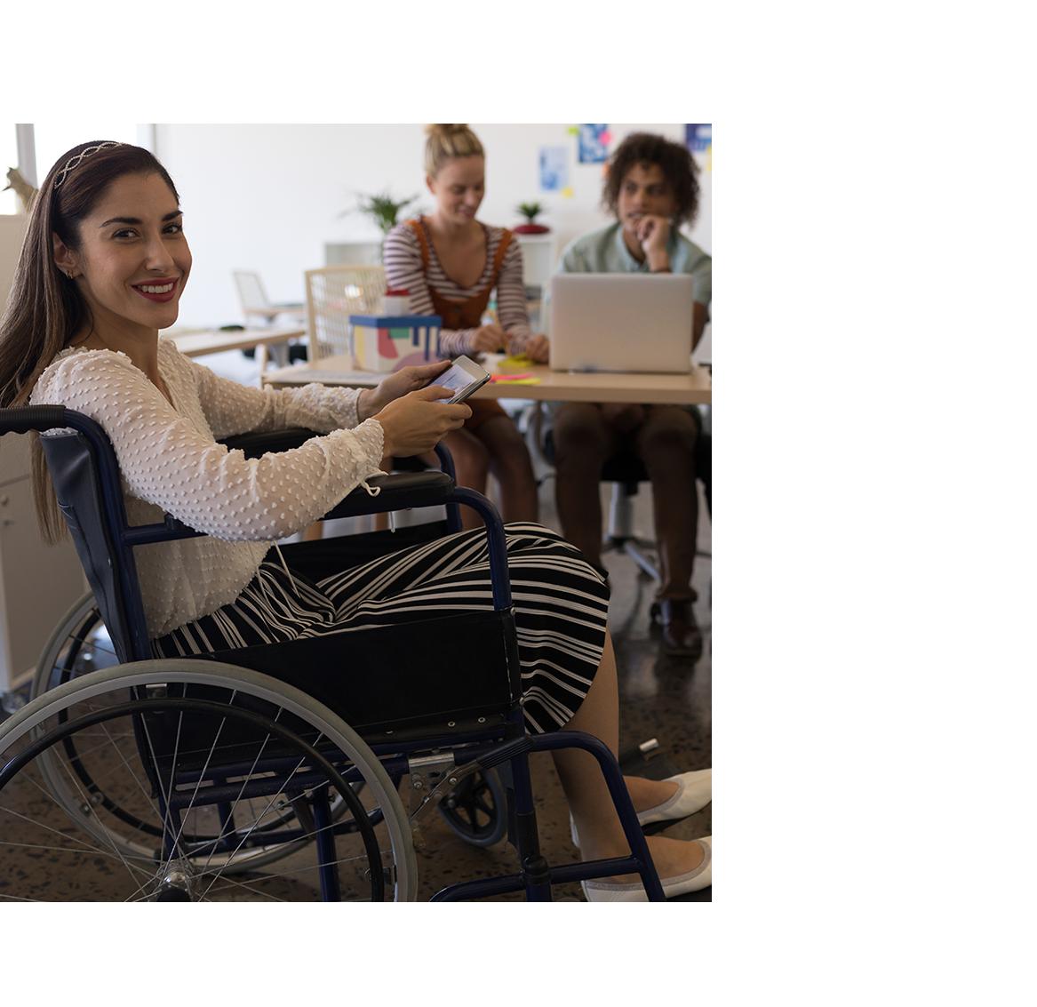 Una mujer en silla de ruedas posa sonriente ante la camara.