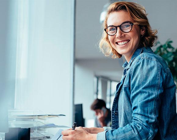 Una mujer con gafas posa con una amplia sonrisa sentada en un escritorio de trabajo.