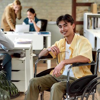 Un hombre en silla de ruedas posa sonriente en una oficina mientras otro hombre trabaja al fondo.