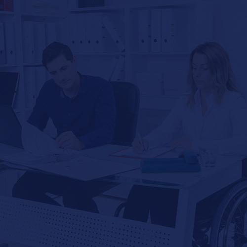Una mujer en silla de ruedas trabaja junto a su compañero de escritorio.