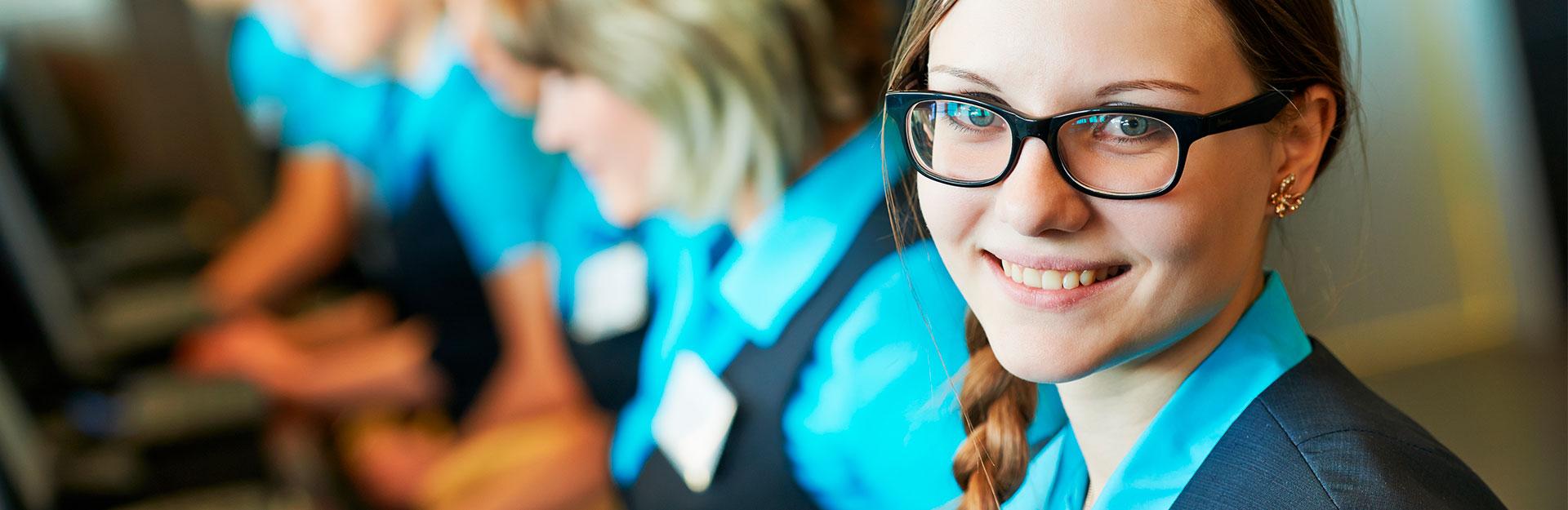 Una empleada posa sonriendo mientras frente a otros trabajadores.