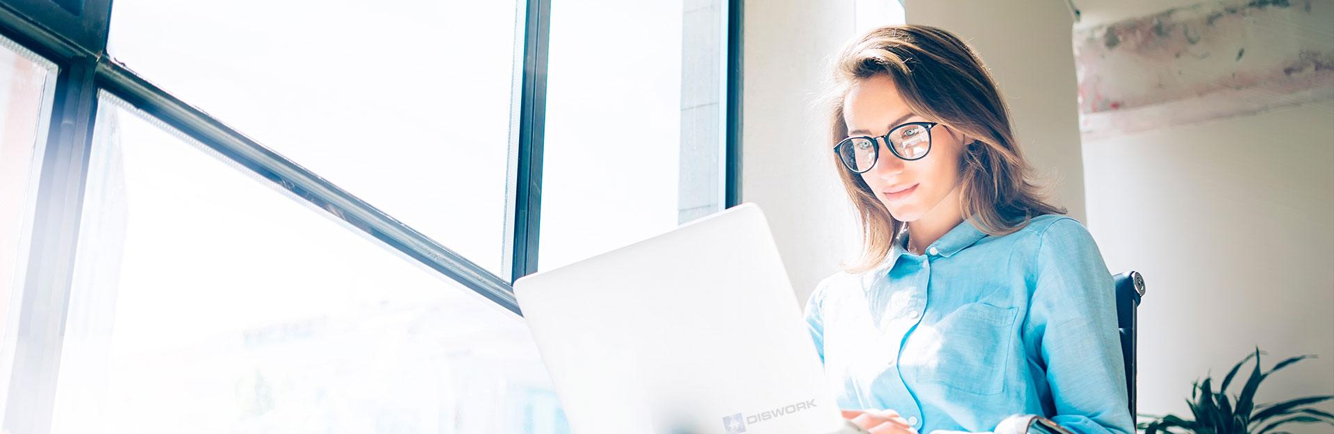 Una mujer con gafas trabaja sentada frente a su ordenador portátil.