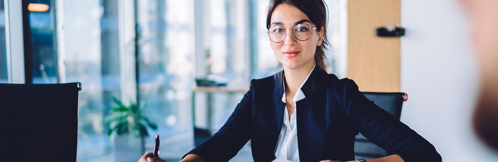 Una mujer trajeada y con gafas posa sentada con una sonrisa en su mesa de trabajo.