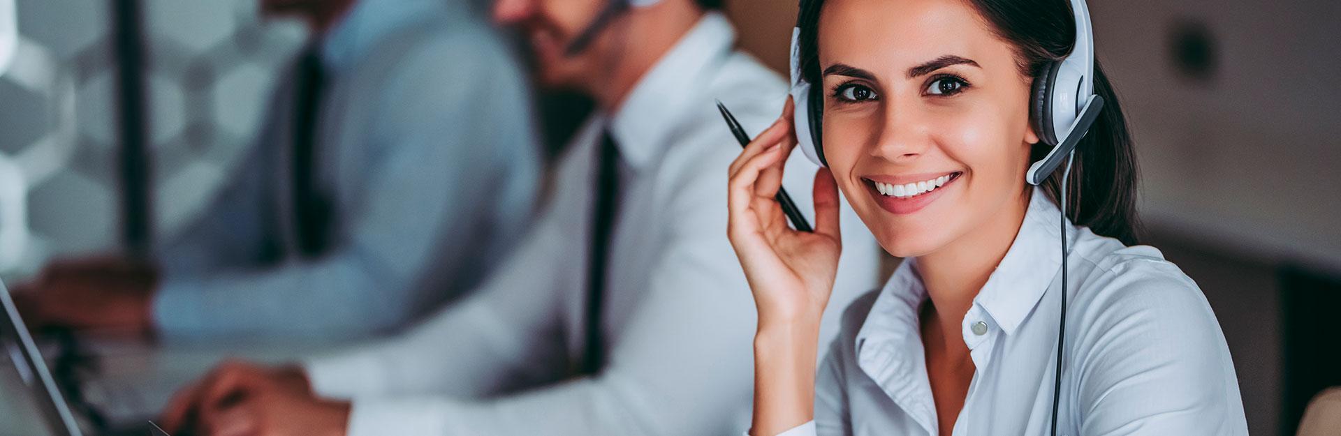 Una operadora de atención al cliente sonríe ante la cámara.