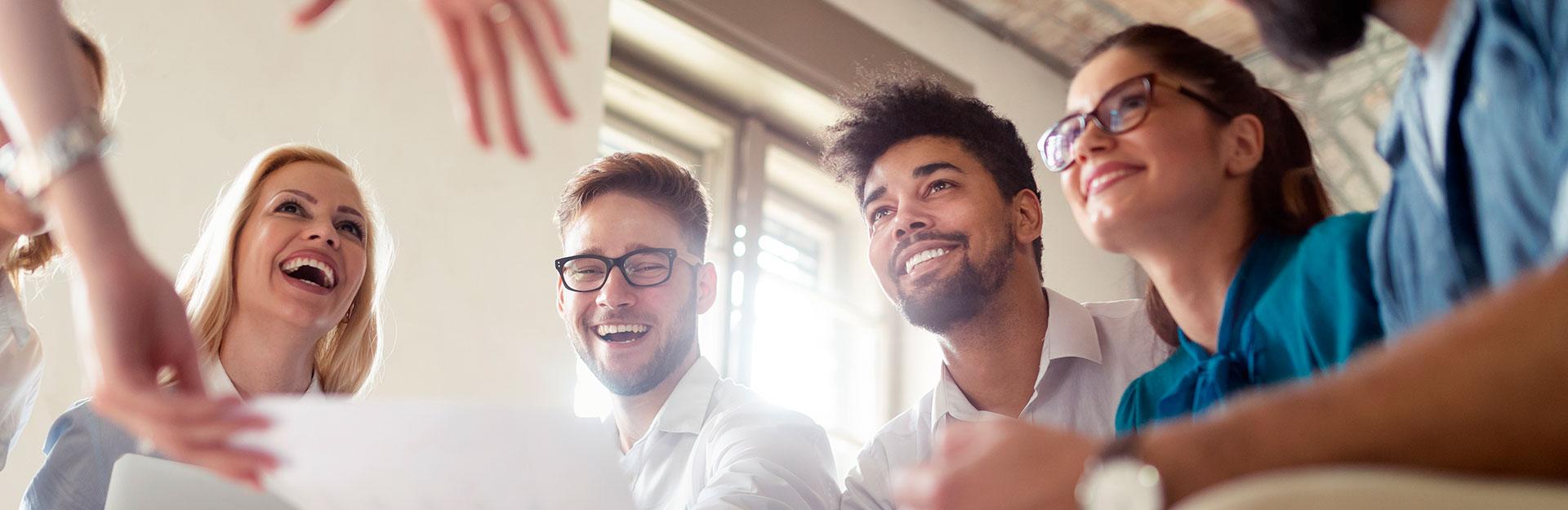 Un grupo de personas trabajan en equipo mientras sonríen.