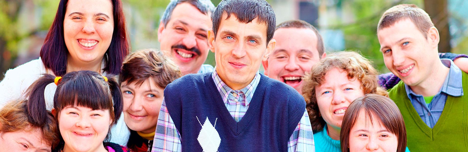 Un grupo de personas con discapacidad sonríen y posan en un parque para una fotografía.