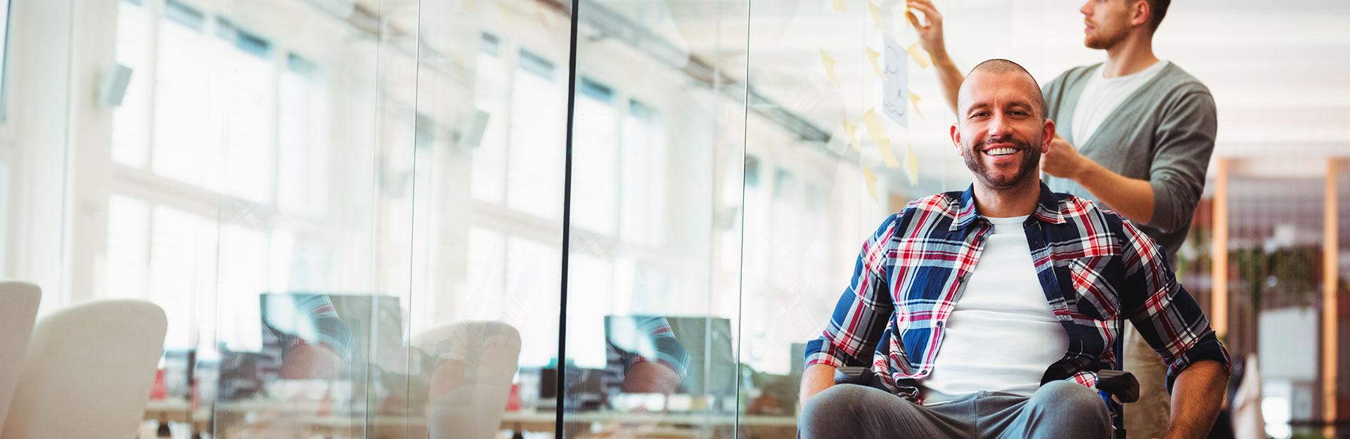 Un empleado en silla de ruedas posa sonriente en una oficina mientras otro trabaja al fondo.