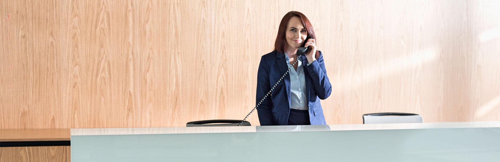 Una recepcionista posa sonriente mientras contesta una llamada de teléfono.