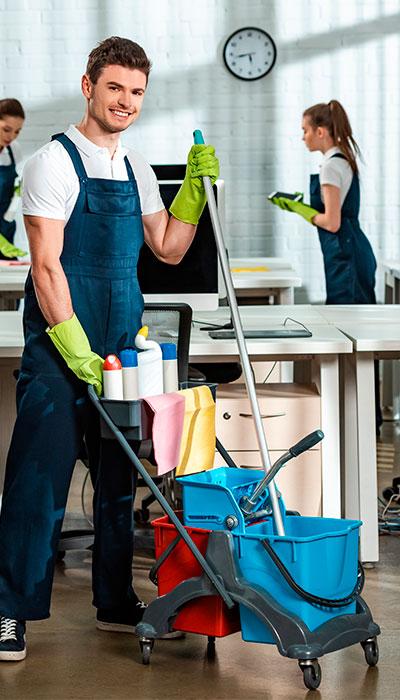 Un empleado de limpieza posa junto a un carrito de limpieza.