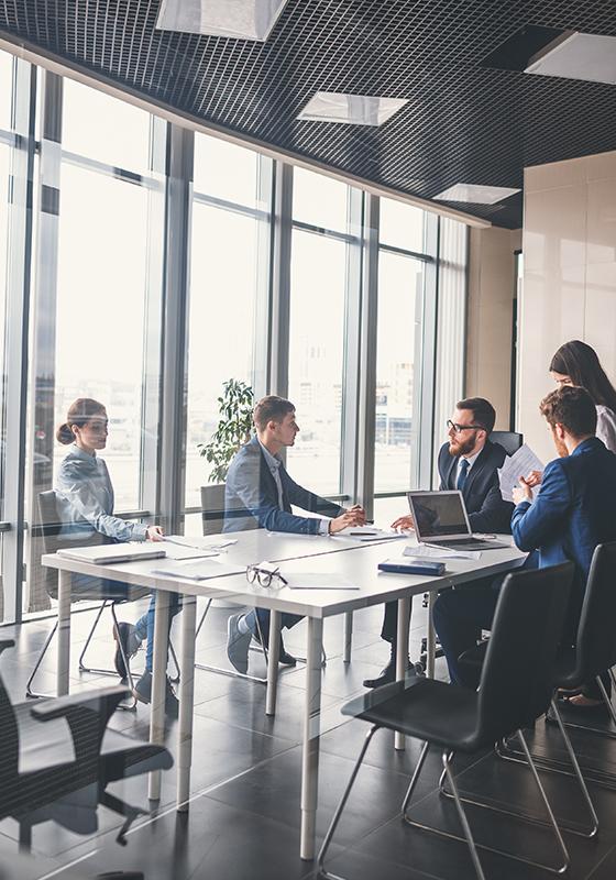 Un grupo de personas trabajan sentados en una sala de reuniones.