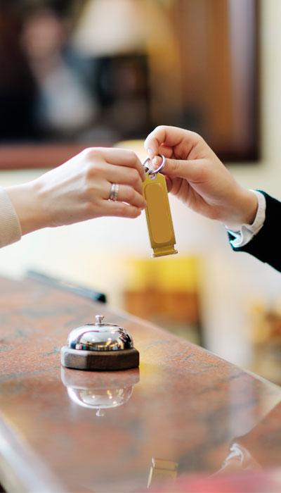 La recepcionista de un hotel entrega las llaves a un huésped.