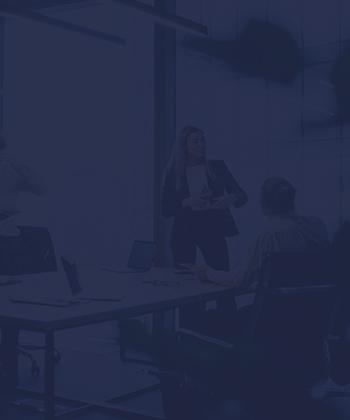 Una mujer trajeada expone una presentación en una sala de reuniones frente a su equipo de trabajo.