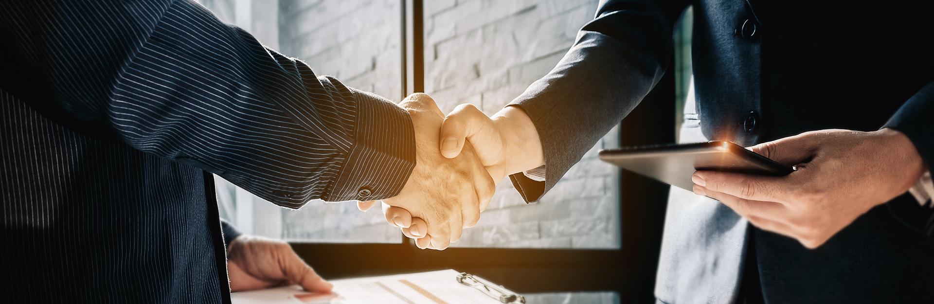 Dos hombres estrechan la mano en una oficina.