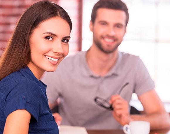 Una mujer y un hombre posan sentados con una amplia sonrisa.