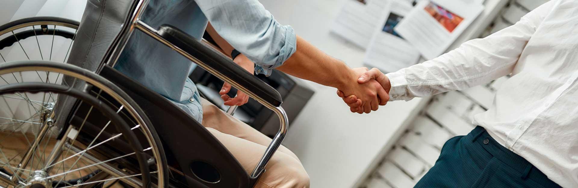 Un empleado en silla de ruedas estrecha la mano con un compañero.
