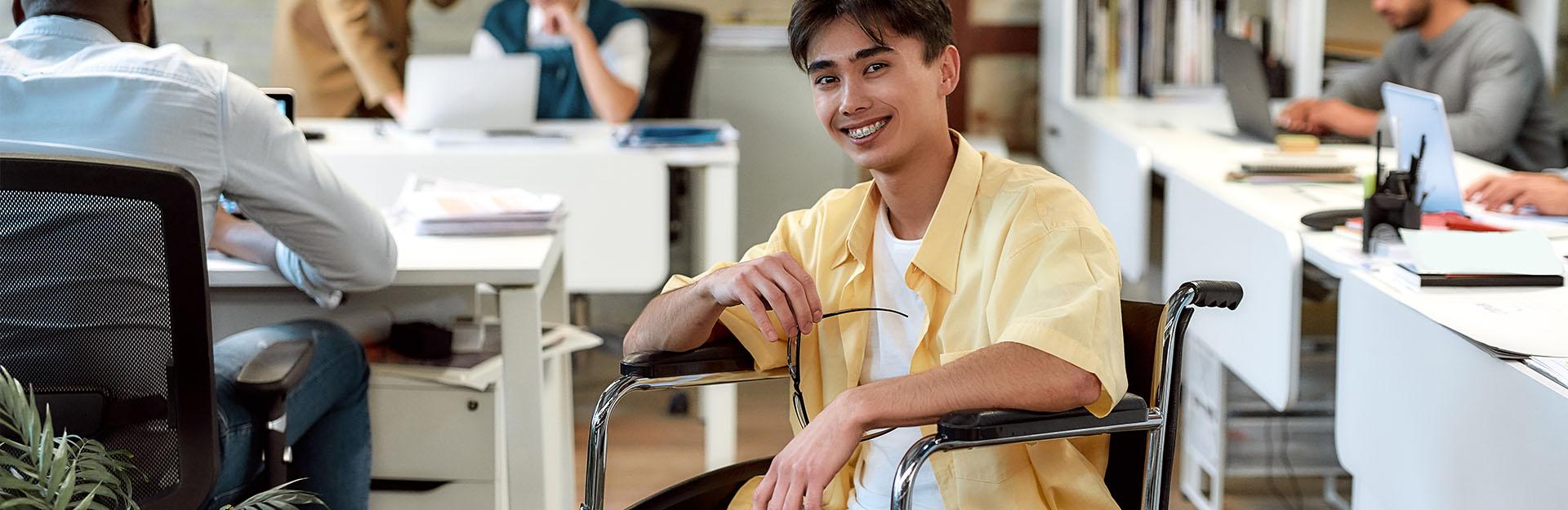 Un chico en silla de ruedas sonríe ante la cámara en una oficina.
