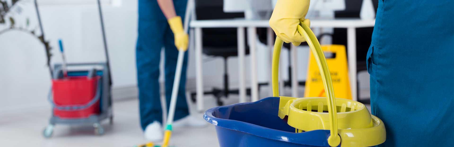 Dos empleados ofrecen un servicio de limpieza en una oficina.