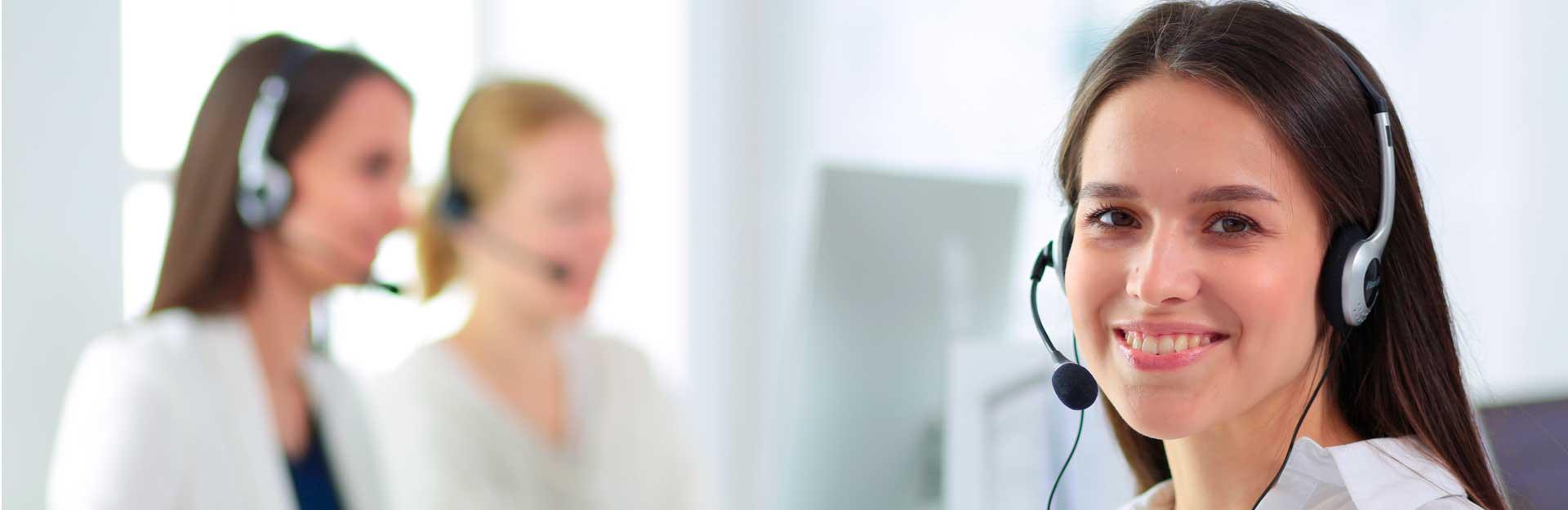 Una empleada sonríe ante la cámara mientras dos compañeras trabajan al fondo.