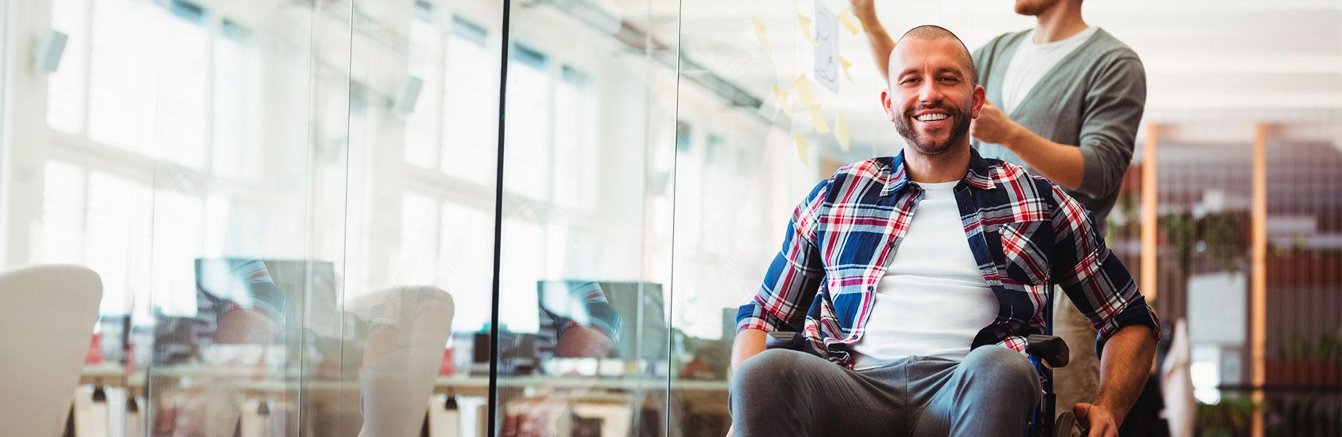 Un hombre en silla de ruedas sonríe en la oficina mientras otro trabaja al fondo.