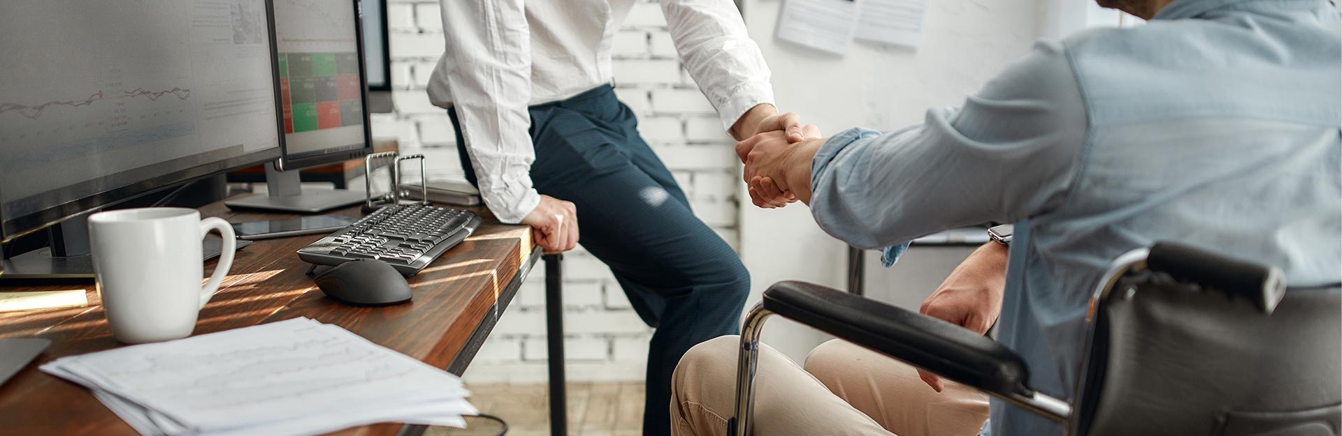 Un hombre en silla de ruedas le estrecha la mano a un compañero de trabajo.